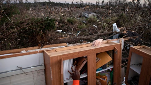 Granadas Baker retrieves personal items from his home after a tornado caused extensive damage to a neighborhood a day earlier in Beauregard, Ala., Monday, March 4, 2019. (AP Photo/David Goldman)