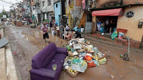Damaged belongings, spoiled food and soaked furniture are piled up in the street to be taken away as trash after flooding in Sao Paulo, Brazil, Monday, March 11, 2019. According to The Sao Paulo state fire department, heavy rains caused the deaths of at least 11 people in and around Brazil's largest city, including a 1-year-old baby. (AP Photo/Andre Penner)