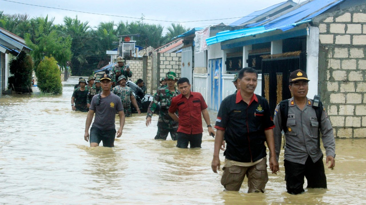 Indonesian police and soldiers search for residents who need assistance at a flooded neighborhood in Sentani, Papua Province, Indonesia, Monday, March 18, 2019. Flash flood and mudslides triggered by days of torrential downpours tore through mountainside villages in Indonesia's easternmost province, killing dozens of people. (AP Photo/Tumbur Gultom)