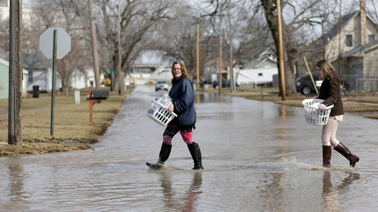 Akashi Haynes, left, and her daughter Tabitha Viers carry their belongings rescued from their flooded home in Fremont, Neb., Monday, March 18, 2019. Authorities say flooding from the Platte River and other waterways is so bad that just one highway lane into Fremont remains uncovered, and access to that road is severely restricted. (AP Photo/Nati Harnik)
