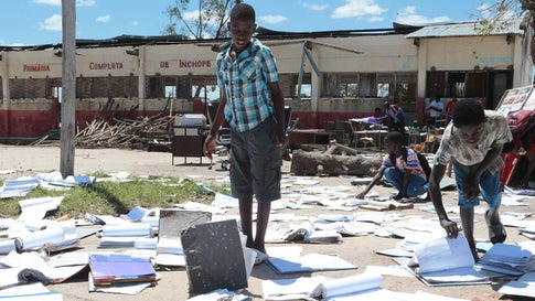 School children pick up books that were left to dry in the sun after their school was damaged by Cyclone Idai, in Inchope Mozambique, Monday March 25, 2019. Cyclone Idai's death toll has risen above 750 in the three southern African countries hit 10 days ago by the storm, as workers rush to restore electricity, water and try to prevent outbreak of cholera. (AP Photo/Tsvangirayi Mukwazhi)