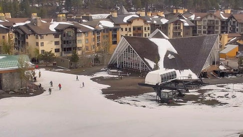 In this webcam image provided by Squaw Valley Alpine Meadows, snow is on the ground at the Squaw Valley Ski Resort base area Wednesday, May 22, 2019, in Olympic Valley, Calif. Memorial Day may be the unofficial start of summer, but California is heading toward the holiday with rainy, windy and snowy weather. The Squaw Valley resort at Lake Tahoe reports it got 32 inches of snow over the past seven days, boosting its season total to 714 inches. Unsettled weather will continue into next week. (Squaw Valley Alpine Meadows via AP)
