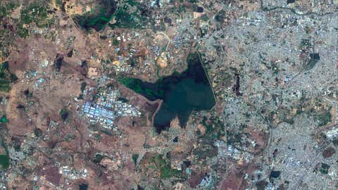 This June 15, 2018, Copernicus Sentinel-2 Satellite image provided by Maxar Technologies shows Chembarambakkam Lake in Chennai, India before the drought. Millions of people are turning to water tank trucks in the southern Indian state of Tamil Nadu as house and hotel taps run dry because of an acute water shortage caused by drying lakes and depleted groundwater. (Copernicus Sentinel-2 Satellite Image/Maxar Technologies via AP)