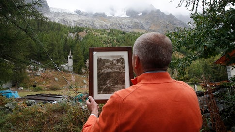 Marco Belfrond holds an old photo the Plancipieux glacier, near Courmayeur, northern Italy, Thursday, Sept. 26, 2019. Italian officials sounded an alarm Wednesday over climate change due to the threat that a fast-moving melting glacier is posing to the picturesque Val Ferret valley near the Alpine town of Courmayeur. The Planpincieux glacier, which spreads 512 square miles across the Grande Jorasses peak of the Mont Blanc massif, has been moving up to nearly 20 inches a day (AP Photo/Antonio Calanni)