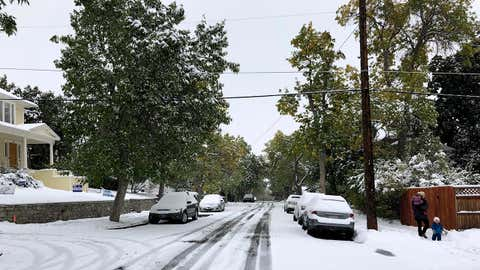 Pedestrians make their way along a snow covered street lined with trees that still have their leaves during a fall snowstorm in Helena, Mont., on Sunday, Sept. 29, 2019. Strong winds and heavy snow caused power outages and temporary road closures in northwestern Montana as a wintry storm threatened to drop several feet of snow in some areas of the northern Rocky Mountains. (AP Photo/Matt Volz)