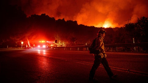 A firefighter crosses Highway 154 while battling the Cave Fire in Los Padres National Forest, Calif., above Santa Barbara on Tuesday, Nov. 26, 2019. (AP Photo/Noah Berger)