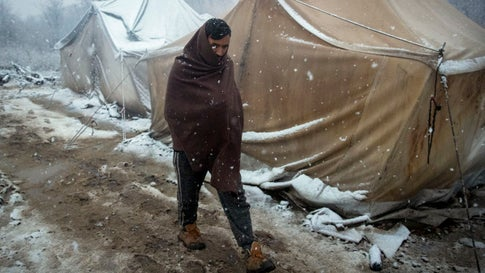A migrant walks amid tents during snowfall at the Vucjak refugee camp outside Bihac, northwestern Bosnia, Monday, Dec. 2, 2019. Despite calls for their relocation before winter, hundreds of migrants remain stuck in a make-shift tent camp in northwestern Bosnia as a spate of snowy and cold weather hit the region. (AP Photo/Darko Bandic)
