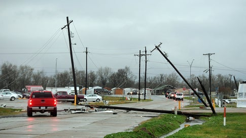 A driver moves around a utility pole knocked down in Alexandria, La., Monday, Dec. 16, 2019, following a severe weather system went through the area. (AP Photo/Brad Kemp)