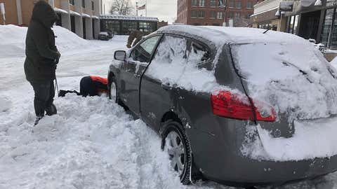 Volunteers help a woman dig out her parked car on Monday, Dec. 30, 2019, after it was blocked by snow from a plow that was clearing snow in downtown Fargo, N.D., after a blizzard that dumped a foot or snow in some areas of the metropolitan area. Authorities warned residents on Saturday to get their cars off the street to help cleaning crews in a process they say could take weeks to complete. Most businesses in the Fargo and Moorhead, Minnesota area were closed or open late on Monday. (AP Photo/Dave Kolpack)