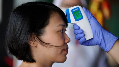 A nurse checks the temperature of a visitor as part of the coronavirus screening procedure at a hospital in Kuala Lumpur, Malaysia, Wednesday, Feb. 5, 2020. More than 100 Malaysians have been quarantined after being evacuated from the Chinese city at the center of a viral outbreak. (AP Photo/Vincent Thian)