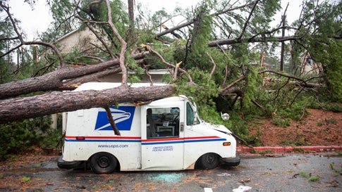 Fallen trees rest on a damaged postal truck at an apartment complex where a reported tornado passed through Thursday, Feb. 6, 2020, in Spartanburg, South Carolina. (AP Photo/Sean Rayford)