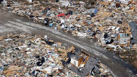 A road separates properties filled with debris Tuesday, March 3, 2020, near Lebanon, Tenn. Tornadoes ripped across Tennessee early Tuesday, shredding more than 140 buildings and burying people in piles of rubble and wrecked basements.  (AP Photo/Mark Humphrey)