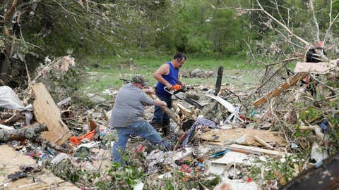 People use a chainsaw to look through debris at a mobile home park after a tornado hit on Monday, April 13, 2020, in Chatsworth, Ga. Severe weather has swept across the South, killing multiple people and damaging hundreds of homes from Louisiana into the Appalachian Mountains. Many people spent part of the night early Monday sheltering in basements, closets and bathroom tubs as sirens wailed to warn of possible tornadoes. (AP Photo/Brynn Anderson)