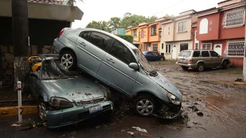 Vehicles stand damaged by an Acelhuate River flash flood at a neighborhood in San Salvador, El Salvador, Sunday, May 31, 2020. According to the Ministry of the Interior, at least seven people died across the country after two days of heavy rains. (AP Photo/Salvador Melendez)