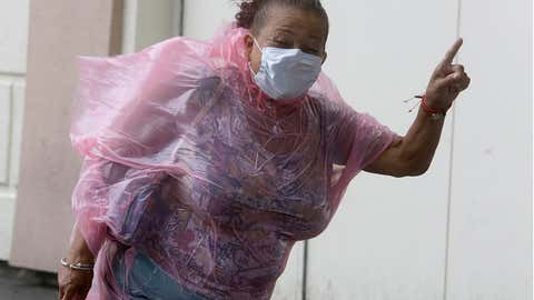A woman shuts her eyes as she struggles to make her way into the Hard Rock Hotel & Casino during heavy winds, Tuesday, Aug. 4, 2020, in Atlantic City, NJ. Tropical Storm Isaias spawned tornadoes and dumped rain during an inland march up the U.S. East Coast, including New Jersey, on Tuesday after making landfall as a hurricane along the North Carolina coast. (AP Photo/Jacqueline Larma)