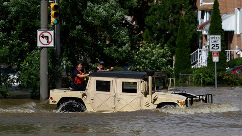 Philadelphia firefighters drive through a flooded neighborhood during Tropical Storm Isaias, Tuesday, Aug. 4, 2020, in Philadelphia. The storm spawned tornadoes and dumped rain during an inland march up the U.S. East Coast after making landfall as a hurricane along the North Carolina coast. (AP Photo/Matt Slocum)