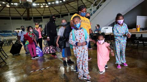 Victoria Nelson with her children Autum Nelson, 2, Shawn Nelson, 7, and Asia Nelson, 6, line up to board a bus to evacuate Lake Charles, La., Wednesday, Aug. 26, 2020, ahead of Hurricane Laura. (AP Photo/Gerald Herbert)