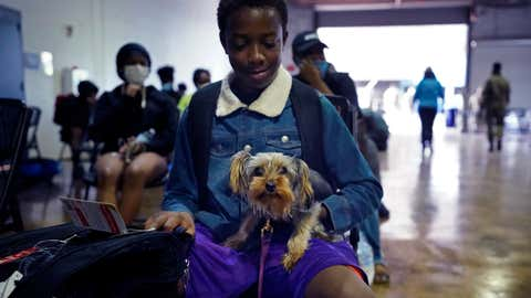 Skyler Brown, 13, holds his dog Chole as they wait to board buses to evacuate Lake Charles, La., Wednesday, Aug. 26, 2020, ahead of Hurricane Laura. (AP Photo/Gerald Herbert)