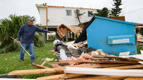 """Mark Andollina, left, removes part of a roof damaged by Hurricane Zeta at the Cajun Tide Beach Resort in Grand Isle, La., Friday, Oct. 30, 2020. Gov. John Bel Edwards says the damage from Zeta was """"catastrophic"""" in Grand Isle, a barrier island community south of New Orleans that was one of the hardest-hit areas.  (AP Photo/Matthew Hinton)"""