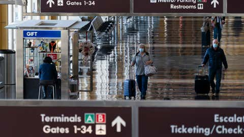 Wearing face masks, travelers walk to and from their planes at Ronald Reagan Washington National Airport, Tuesday, Nov. 24, 2020, in Arlington, Va., in advance of the Thanksgiving holiday. (AP Photo/Jacquelyn Martin)
