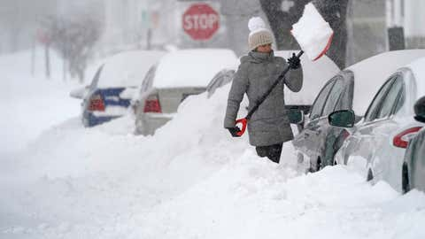 A woman throws a shovel full of snow while digging out her car.  On Thursday morning, December 17, 2020, in Manchester, NH South New Hampshire, a winter storm is expected to cover the snow with snow all day.  (AP photo / Charles Krupa)