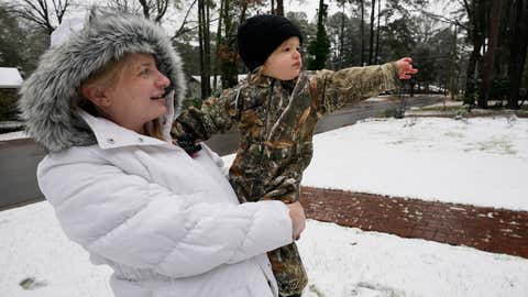 Luke West, 21 months, point out the snow covered yard to his mother, Anna Laura West, in Jackson, Miss., Monday morning, Jan. 11, 2021. A winter storm coated parts of Texas, Louisiana and Mississippi with snow on Sunday and into Monday morning. (AP Photo/Rogelio V. Solis)
