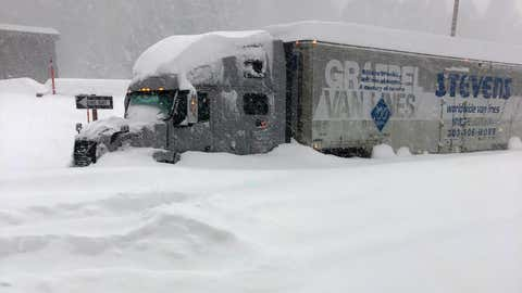 In this photo provided by Caltrans District 9, a tractor trailer that is stuck in heavy snowfall at Crestview along U.S. Hwy 395, closed in Mono County, Calif., Wednesday, Jan. 27, 2021. An atmospheric river storm pumped drenching rains into the heart of California on Thursday as blizzard conditions buried the Sierra Nevada in snow. (Andy Richard/Caltrans District 9 via AP)