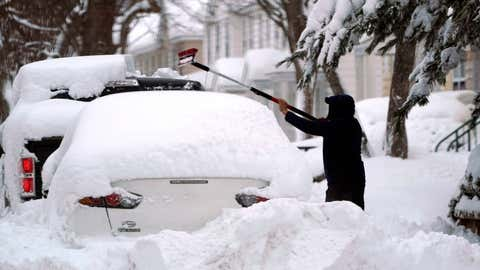 A man brushes snow off a car, Tuesday, Feb. 2, 2021, in Lawrence, Mass. A sprawling, lumbering winter storm has walloped the Eastern U.S., shutting down coronavirus vaccination sites, closing schools and halting transit. (AP Photo/Elise Amendola)