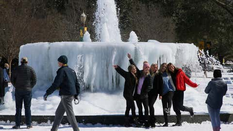 Baylor University students enjoy their snow day without classes while posing near a fountain on campus Monday, Feb. 15, 2021, in Waco, Texas. Arctic temperatures caused a massive power outage and brought traffic to a crawl. (Rod Aydelotte/Waco Tribune Herald via AP)