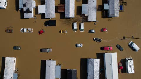 In this photo taken by a drone, a boat weaves through partially submerged cars and trailers in the city of Beattyville, Ky., following heavy rains which caused the Kentucky River to flood, Tuesday, March 2, 2021. (Alex Slitz/Lexington Herald-Leader via AP)