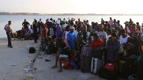 A line of people waits for evacuation to Nassau at the Port in Marsh Harbour on Abaco Island, on Saturday, September 7, 2019. (AP Photo/Fernando Llano)
