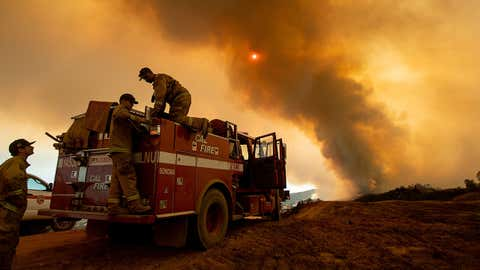 Firefighter Joe Smith retrieves supplies while battling the Ranch Fire, part of the Mendocino Complex Fire, burning along High Valley Rd near Clearlake Oaks, California, on August 5, 2018. (NOAH BERGER/AFP/Getty Images)