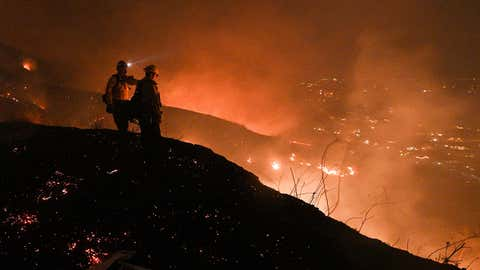 TOPSHOT - Firefighters look out over a burning hillside as they fight the Blue Ridge Fire in Yorba Linda, California, October 26, 2020. - Some 60,000 people fled their homes near Los Angeles on October 26 as a fast-spreading wildfire raged across more than 7,200 acres (3,000 hectares), blocking key roadways and critically injuring two firefighters. (Photo by Robyn Beck / AFP) (Photo by ROBYN BECK/AFP via Getty Images)