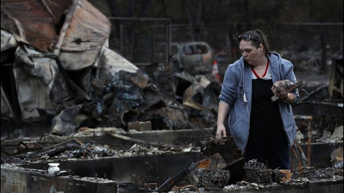 Brandy Powell looks through the remains of her home, destroyed by the Camp Fire two weeks earlier, on November 22, 2018 in Paradise, California.
