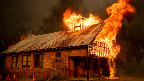 An historic schoolhouse burns as the Carr Fire tears through Shasta, California, on Thursday, July 26, 2018. The wildfires have been fueled by high temperatures, wind and low humidity in the area. Noah Berger/Associated Press
