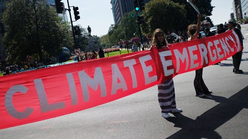 Activists hold a banner while blocking a major intersection during climate protests in Washington on September 23, 2019. (Mandel Ngan/AFP via Getty Images)