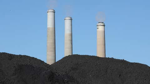 Piles of coal sit in front of three stacks as emissions are vented from them at PacifiCorp's 1,320-megawatt coal-fired Hunter power plant on June 19, 2019, in Castle Dale, Utah. (George Frey/Getty Images)