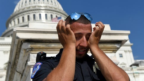 A police officer wipes sweat from his eyes as he stands his post on the west side of Capitol Hill in Washington, Saturday, July 20, 2019. (AP Photo/Susan Walsh)