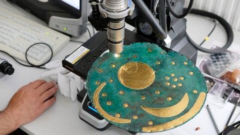 03.06.2019, Sachsen-Anhalt, Halle: Zu Demonstrationszwecken wird in der Werkstatt vom Landesamt für Denkmalpflege und Archäologie Sachsen-Anhalt eine Nachbildung der Himmelsscheibe von Nebra mit einem Mikroskop untersucht. (zu dpa «Forscher entdecken neue Goldspuren auf Himmelsscheibe von Nebra») Foto: Sebastian Willnow/dpa-Zentralbild/dpa +++ dpa-Bildfunk +++