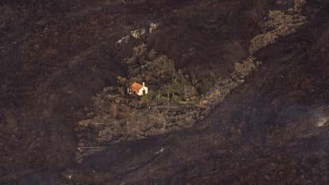 Spanien, La Palma: Lava von einem Vulkanausbruch umgibt ein Haus auf der Insel La Palma. Der Vulkanausbruch auf der kleinen Kanaren-Insel La Palma hat Hunderte Häuser zerstört - eines ist jedoch auf wundersame Weise verschont geblieben.