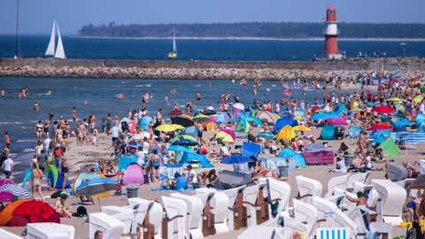 Bei sommerlichen Temperaturen und Sonnenschein zieht es Urlauber und Einwohner an die Strände entlang der Ostsee, wie hier in Warnemünde.