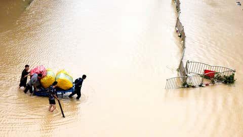 21.07.2021, China, Zhengzhou: Anwohner tragen nach der schweren Überschwemmung in zentralchinesischen Provinz Henan ihre Habseligkeiten über eine überflutete Straße. Chinas Militär hat einen Damm gesprengt, um das Hochwasser abzulassen, das eine der am dichtesten besiedelten Provinzen des Landes bedroht. Foto: Zhu Xiang/Xinhua/dpa +++ dpa-Bildfunk +++