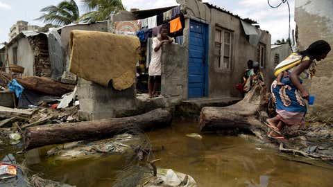 dpatopbilder - 27.03.2019, Mosambik, Beira: Eine Frau mit einem Baby auf dem Rücken (r) versucht den Kontakt mit verschmutztem Wasser zu vermeiden. Nach dem verheerenden Zyklon «Idai» sind in Mosambik die ersten Fälle der schweren Durchfallerkrankung Cholera bestätigt worden. Foto: Themba Hadebe/AP/dpa +++ dpa-Bildfunk +++