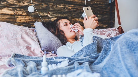 Shot of a young woman using a smartphone while sick in bed at home