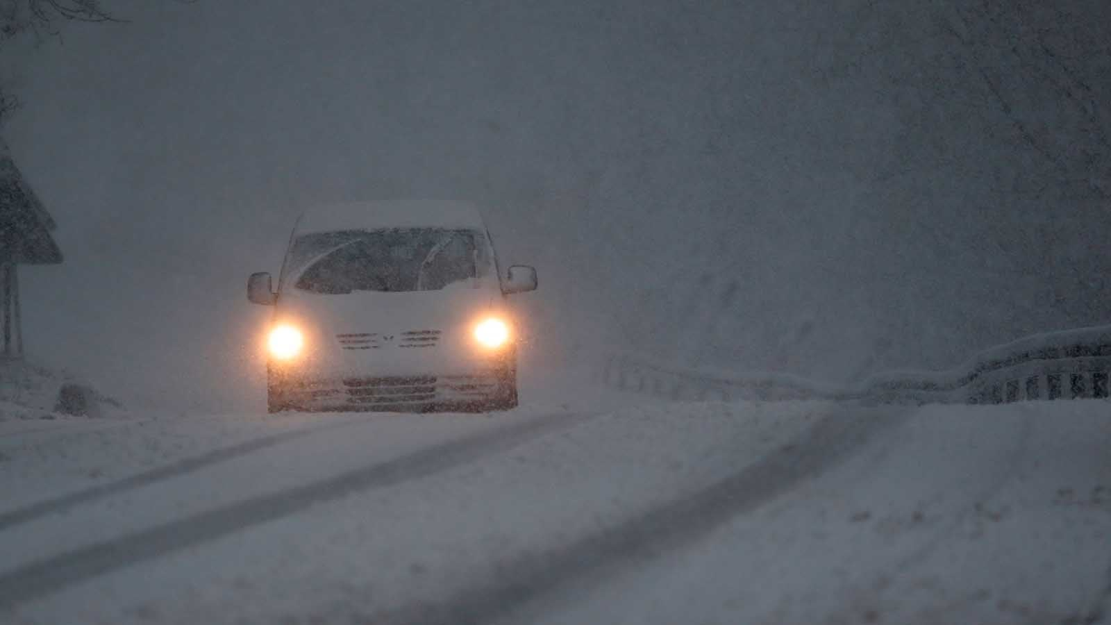 A car drives through a snow storm on a road near Sarajevo, Bosnia, Monday, Feb. 11, 2019. Heavy snow descended on the Balkan countries causing havoc throughout the region. (AP Photo/Amel Emric)