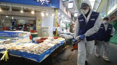 24.02.2020, Südkorea, Seoul: Arbeiter in Schutzkleidung sprühen Desinfektionsmittel auf einem Markt in Seoul als Vorsichtsmaßnahme gegen das Coronavirus. Die südkoreanischen Gesundheitsbehörden haben zwei weitere Todesfälle in Verbindung mit dem Coronavirus gemeldet. Foto: Ahn Young-Joon/AP/dpa +++ dpa-Bildfunk +++