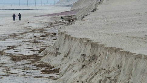 """13.02.2020, Niedersachsen, Wangerooge: Besucher spazieren an der Abbruchkante des Strandes. Die Sturmflut der letzten Tage hat ca 50 Tausend Kubikmeter Sand abgetragen und in die Nordsee gespült. (zu dpa: """"Kein Strand, keine Touristen? «Sabine» stellt Wangerooge vor Herausforderung"""") Foto: Patrik Stollarz/dpa +++ dpa-Bildfunk +++"""
