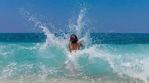 Little kid enjoying the waves on the beach