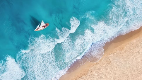Waves and yacht from top view. Turquoise water background from top view. Summer seascape from air. Top view from drone. Travel-image