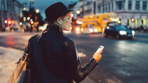 Girl in the city of London using mobile app for taxi calling